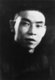 Du Yuesheng (Tu Yüeh-sheng), commonly known as 'Big-Ears Du' (1887–1951) was a Chinese gangster who spent much of his life in Shanghai. He was a key supporter of the Kuomintang (KMT; aka Nationalists) and Chiang Kai-shek in their battle against the Communists during the 1920s, and was a figure of some importance during the Second Sino-Japanese War.<br/><br/>  After the Chinese Civil War and the KMT's retreat to Taiwan, Du went into exile in Hong Kong and remained there until his death in 1951. According to a contemporaneous description:<br/><br/>  Du Yuesheng is short and slender, with long arms, a shaven head, large yellow teeth and large ears that stick out. He is always accompanied by armed bodyguards, and his home is a fortified drug depot, well stocked with guns and ammunition. Upon entering, the visitor finds the entrance hall lined on both sides with stacks of rifles and sub-machine guns. The house has three floors - on each floor he keeps one of his three wives. He speaks no foreign languages, yet is always keen to meet people of all nationalities, for he gleefully collects gossip and information, no matter how seemingly trivial.<br/><br/>  Du employs four bodyguards: an ill-tempered blacksmith called Fiery Old Crow, a gardener, a former waiter from the Shanghai Club who speaks English and a former chauffeur from the American consulate called Stars & Stripes. Du never goes anywhere without being accompanied by two carloads of armed men. If going out on the town to teahouses and nightclubs, one car always goes ahead to check the place out first. Du follows in his bullet proof car with a second car full of his enforcers. Only when his men have surrounded the car door does he get out. Once inside the club, his guards all sit around him with their guns in plain sight to everyone.